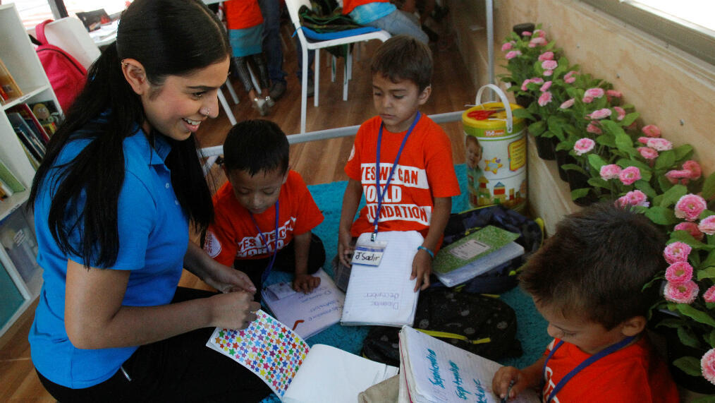 Una profesora interactúa con niños migrantes en una clase de inglés dentro de un autobús convertido en un salón de clases como parte del programa 'Escuelas sobre ruedas' de la organización Yes We Can de California, Tijuana, México, el 2 de agosto de 2019.