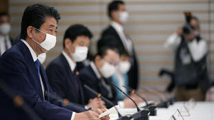 Shinzo Abe (left) chairs a meeting on the coronavirus crisis at the official residence of the Japanese prime minister on April 6, 2020 in Tokyo.