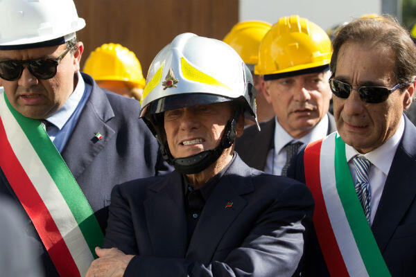 Silvio Berlusconi wears a firefighter's helmet as he visits a village struck by an earthquake on the island of Ischia on October 14, 2017.