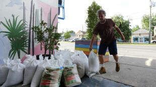 أحد سكان نيو أورليانز يضع أكياس الرمل أمام مقر عمله استعدادا لوصول العاصفة باري في 12 تموز/يوليو 2019