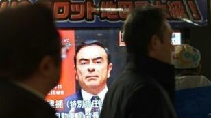 مارة يتابعون برنامجا عن الرئيس السابق لمجلس إدارة مجموعة نيسان لصناعة السيارات على شاشة تلفزيون في محل تجاري في طوكيو في 21 كانون الأول/ديسمبر 2018