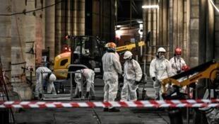 Des ouvriers lors de travaux préliminaires dans la cathédrale Notre-Dame, le 17juillet2019 à Paris.