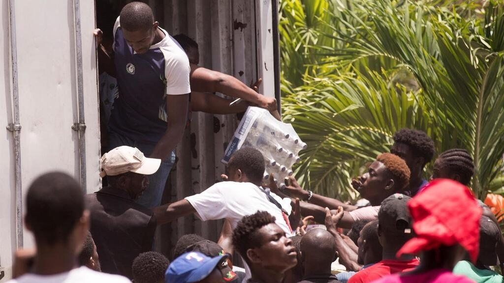 LOS CAYOS (HAITÍ), 21/08/2021.- Personas saquean un camión con ayuda alimentaria hoy, en Les Cayes (Haití). El terremoto registrado el sábado pasado, de magnitud 7,2, afectó principalmente al sur de Haití, causó al menos 2.189 muertos y 12.268 heridos, y dejó 332 desaparecidos, según el último balance oficial, divulgado el pasado miércoles.