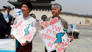 Habitantes de Corea del Sur portan banderas de la unificación previo a la cumbre a desarrollarse el viernes en la zona desmilitarizada. Abril 26 de 2018.