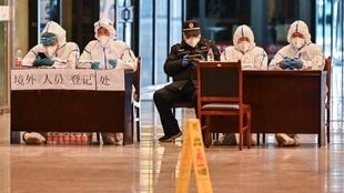 موظفون ببزات واقية  بانتظار وصول الركاب في محطة قطارات ووهان بتاريخ 28 آذار/مارس 2020