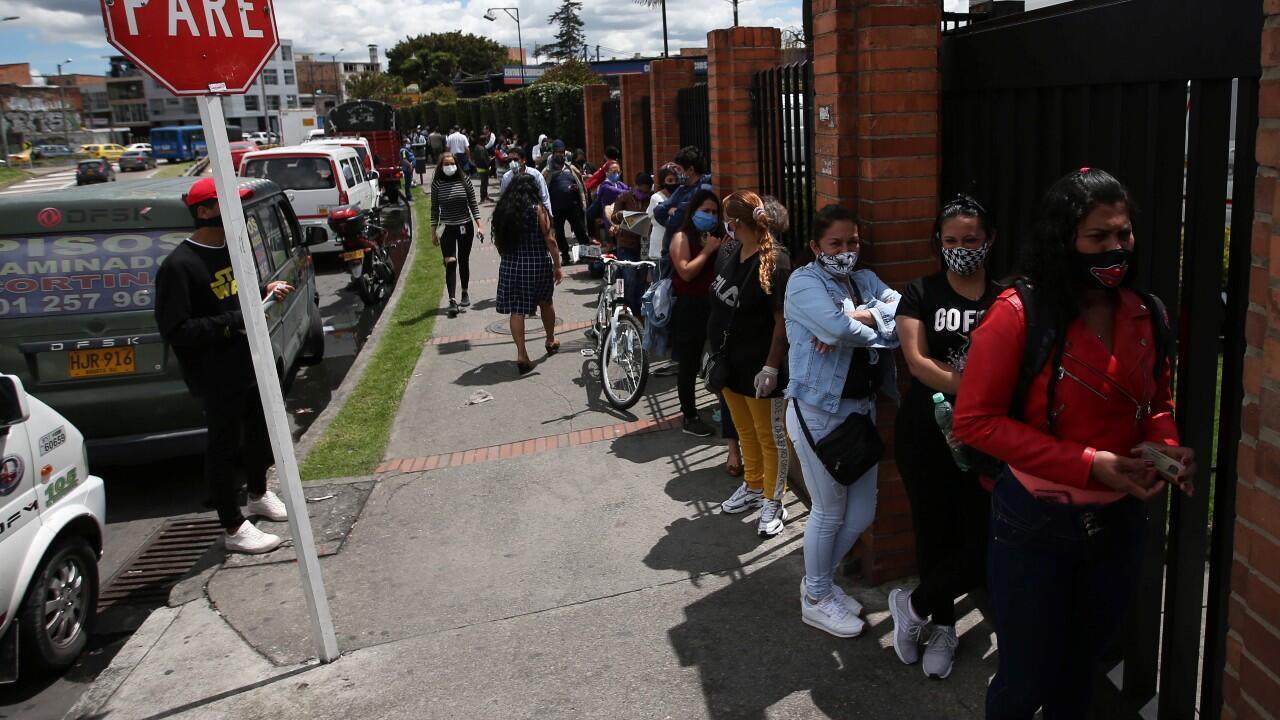 Un grupo de personas utilizando mascarilla hace una fila, para entrar a comprar en un súper mercado, en Bogotá, Colombia, el 19 de junio de 2020.