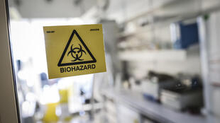 A picture taken in a laboratory of the National Reference Center (CNR) for respiratory viruses at the Institut Pasteur in Paris on January 28, 2020 shows a biohazard sticker on the entrance of a room. The CNR analyses for respiratory viruses among which coronavirus.
