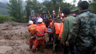 Des secouristes transportant un rescapé du tremblement de terre le 8 août dans le district de Puge, en Chine.