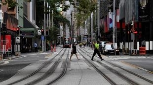 People cross a quiet road in central Sydney on March 25, 2020, as people stay away due to restrictions to stop the spread of the worldwide COVID-19 coronavirus outbreak