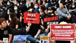 Des milliers de manifestants se sont rassemblés dans le hall de l'aéroport de Hong Kong, le 26 juillet 2019, dans le but de sensibiliser les voyageurs.