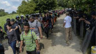 Des migrants centraméricains traversent le fleuve Suchiate, frontière entre le Mexique et le Guatemala, sous la bonne garde de la police mexicaine.