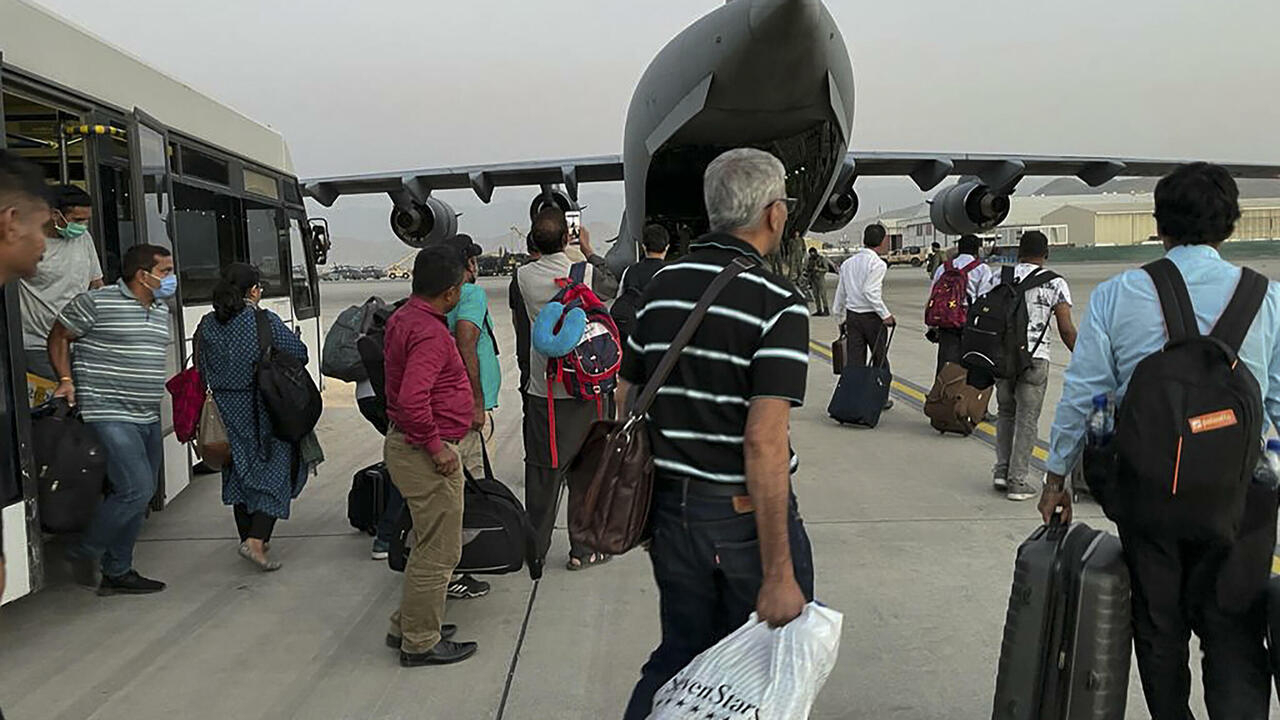 Indian nationals prepare to board an Indian military aircraft to be evacuated after the Taliban takeover of Afghanistan