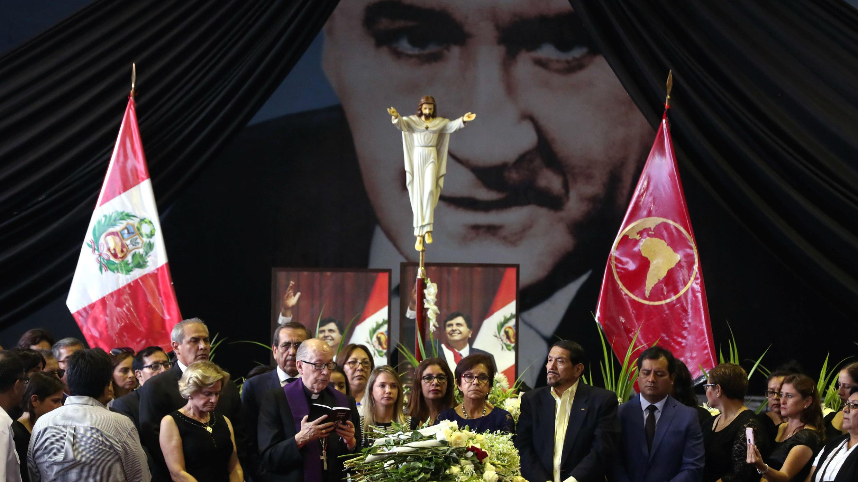 El Arzobispo Juan Luis Cipriani, Pilar Nores, ex esposa del ex presidente de Perú, Alan García, familiares y amigos se reúnen alrededor del ataúd durante un velatorio, después de que García se disparara el miércoles, en Lima, Perú, el 18 de abril de 2019.