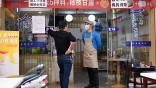 Dos empleados de un restaurante con mascarillas esperan a los clientes en Huanggang, en la provincia de Hubei (China), el 26 de marzo de 2020