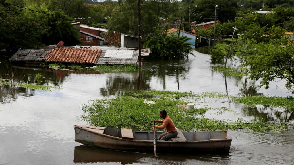 Se ve a un hombre en un bote en una calle inundada después de las fuertes lluvias que causaron el desbordamiento del río Paraguay, en un vecindario en las afueras de Asunción, Paraguay, el 26 de mayo de 2019.
