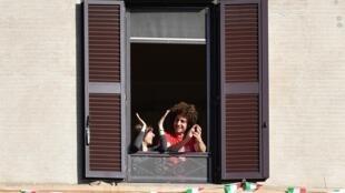 Des Italiens applaudissent depuis leur fenêtre l'assouplissement du confinement, à Rome le 3 mai 2020