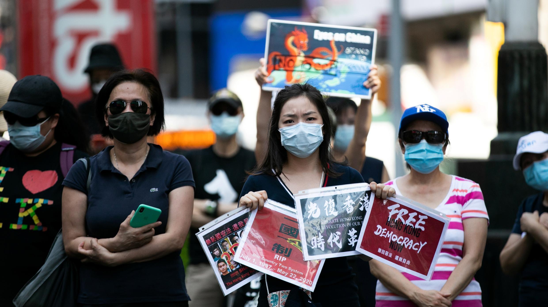 Los manifestantes que apoyan el movimiento prodemocrático de Hong Kong con máscaras protectoras tienen carteles en Times Square, en el distrito de Manhattan de Nueva York, Nueva York, EE. UU., El 2 de agosto de 2020.