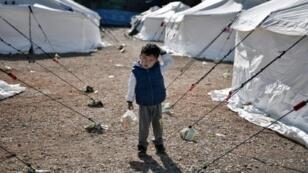 طفل يحمل كيس خبز في مركز لإيواء اللاجئين قرب أثينا في 25 شباط/فبراير 2016