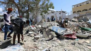 Ciudadanos de Mogadiscio en medio de los escombros dejados por la explosión de un carro bomba, el 2 de septiembre de 2018.