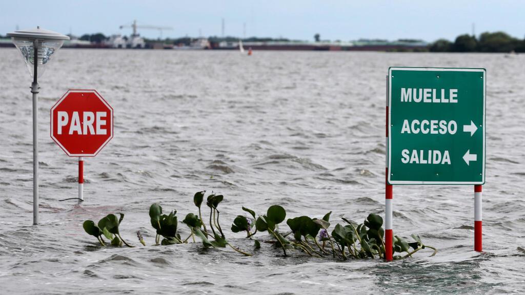 Las señales se ven en una calle inundada después de las fuertes lluvias que causaron el desbordamiento del río Paraguay, en un vecindario en las afueras de Asunción, Paraguay, el 26 de mayo de 2019.