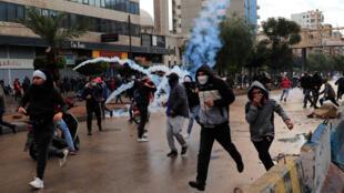 Des manifestants fuient les bombes lacrymogènes lors d'une manifestation contre la détérioration des conditions de vie et les mesures strictes de confinement, à Tripoli, dans le nord du Liban, le 28 janvier 2021.
