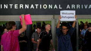 """Un hombre sostiene un letrero que dice """"Bienvenidos refugiados"""" en la terminal internacional de llegadas del Aeropuerto Internacional de los Ángeles, en los Ángeles California el 29 de junio del 2017."""