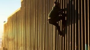 A Honduran migrant climbs the US-Mexico border fence on December 8, 2018