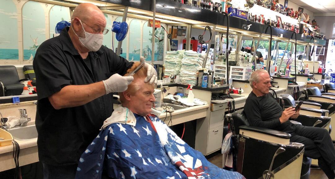 El barbero Tommy Thomas, de 69 años, quien lleva 50 años cortando el pelo, le corta el pelo a su cliente Fred Bentley después de que el gobernador de Georgia permitiera abrir un número selecto de negocios durante las restricciones de la enfermedad por coronavirus en Atlanta, Georgia, EE. UU. 24 de abril de 2020.