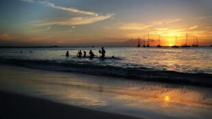 Turistas juegan en el agua en una playa mientras se pone el sol en Bridgetown, Barbados, el 24 de marzo de 2017.