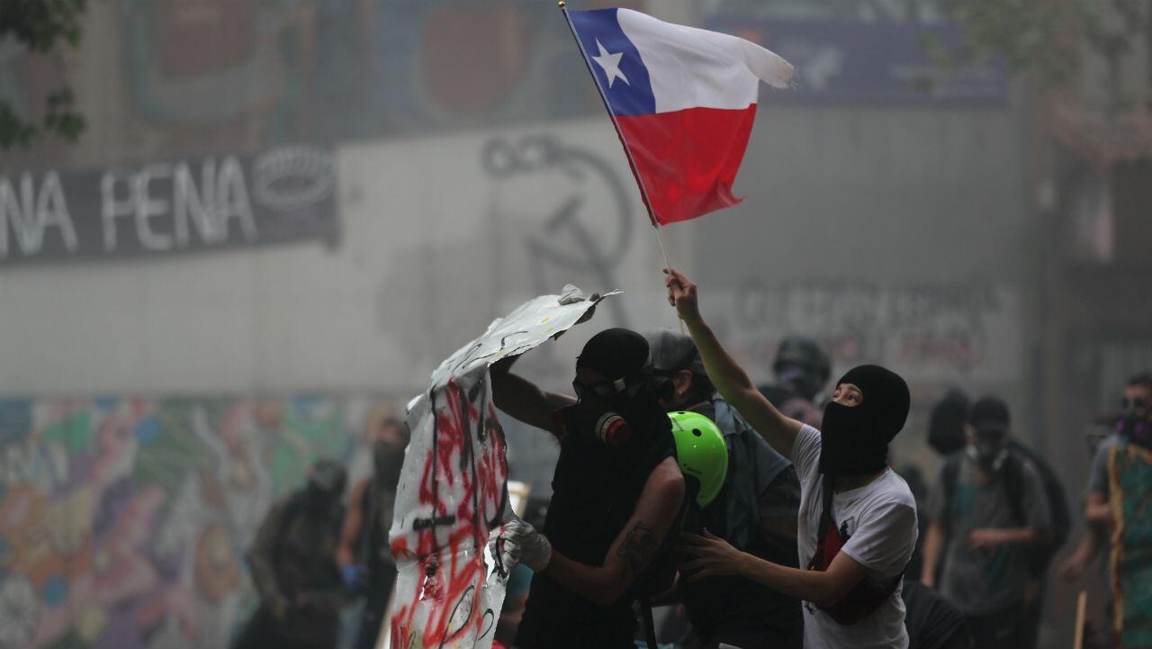 Los manifestantes agitan una bandera durante una protesta contra el gobierno en Santiago, Chile 11 de noviembre de 2019.