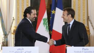 الرئيس الفرنسي إيمانويل ماكرون يصافح رئيس الوزراء اللبناني المستقيل سعد الحريري