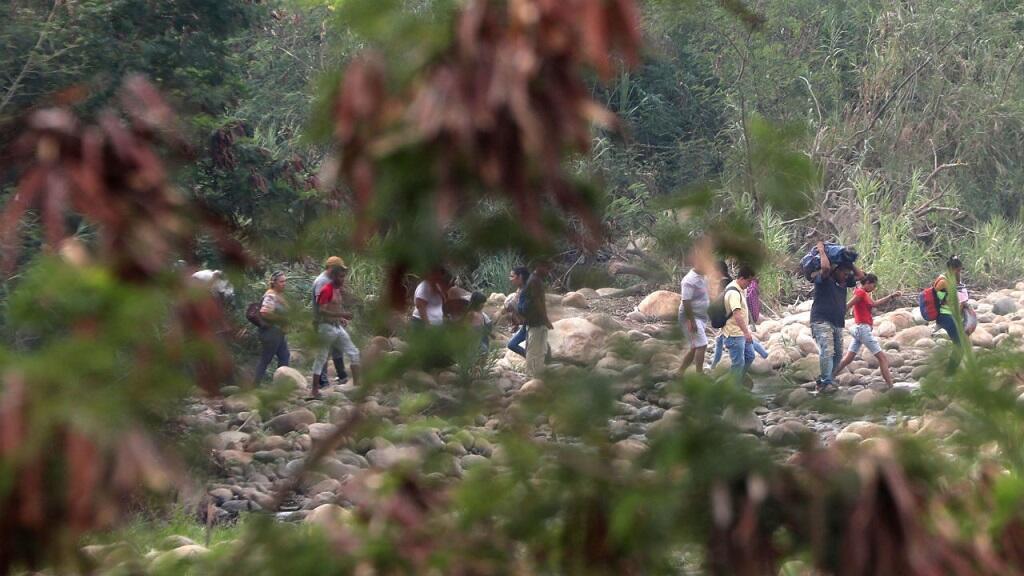 Un grupo de personas cruza la frontera colombo-venezolana de forma ilegal por las trochas cercanas al puente Simón Bolívar, este miércoles 27 de febrero, en Cúcuta (Colombia).