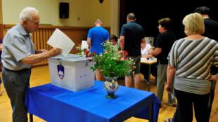 La gente vota en un colegio electoral durante las elecciones generales en Kamnik, Eslovenia, el 3 de junio de 2018.