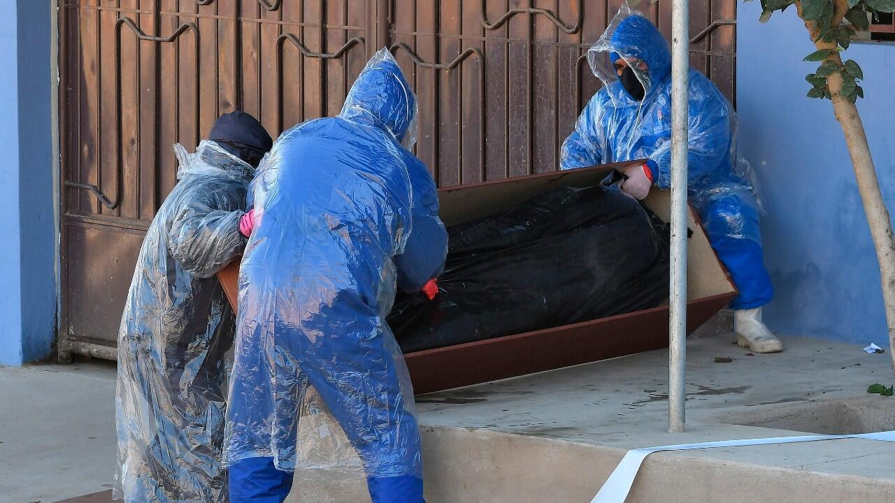 Empleados de una funeraria retiran el cuerpo sin vida de un hombre que permaneció durante horas abandonado en una calle, tras aparentemente fallecer por Covid-19, en Cochabamba, Bolivia, el 5 de julio de 2020.EFE/