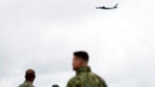 NATO forces on the USS Moutn Whitnes watch a Russian Tupolev TU-142 fly past