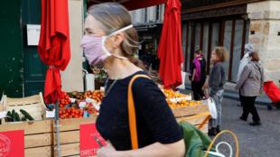 Une femme fait ses courses avec un masque à Paris, le 19 avril 2020.