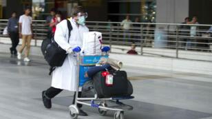 Un passager se dirige vers une ambulance à son arrivée à l'aéroport de New Delhi.