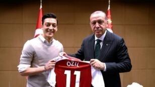 أوزيل يلتقط صورة بقميصه مع الرئيس التركي رجب طيب أردوغان في 13 أيار/مايو 2018.