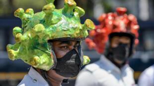 Des policiers indiens portent un casque en forme de virus pour sensibiliser la population aux risques de contamination du coronavirus