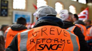 """Un trabajador ferroviario usa un chaleco sobre el que se lee """"huelga reforma"""" durante una manifestación en la estación de Saint-Charles en Marsella"""