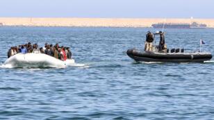 Des garde-côtes libyens escortent le 6 juin 2015 des migrants qui cherchent à gagner l'Europe en traversant la Méditerranée sur un bateau de fortune.