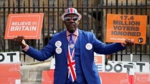 Un partidario pro-Brexit sostiene pancartas fuera del Parlamento, en Londres, el 28 de marzo de 2019.