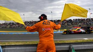 Un supervisor de carrera  ondea las banderas amarillas durante la 87a edición de las 24 Horas de la carrera de Le Mans, el 15 de junio de 2019, en Le Mans, al noroeste de Francia.