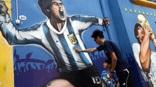 A man and his child pay tribute next to a mural depicting Argentine football legend Diego Maradona  in Buenos Aires on November 25, 2020, on the day of his death