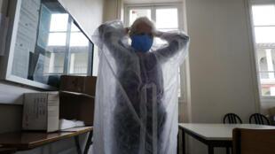 Une responsable de la communication des hôpitaux de Saint-Maurice, en région parisienne, enfile une tenue de protection le 8 mai 2020
