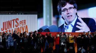 """El depuesto líder catalán Carles Puigdemont aparece en una pantalla durante un evento de su plataforma política """"Junts per Catalunya"""" para marcar el inicio oficial de la campaña electoral de las elecciones regionales de Cataluña en Barcelona, España, el 4 de diciembre de 2017."""