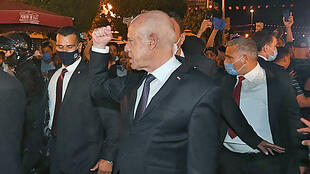 Tunisian President Kais Saied gestures to supporters in Tunis after he suspended parliament for 30 days, seen here in a picture by the Tunisian Presidency on July 26, 2021