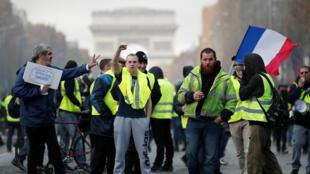 """Integrantes del movimiento de los """"chalecos amarillos"""" marchan en los Campos Eliseos en París, el 24 de noviembre de 2018."""