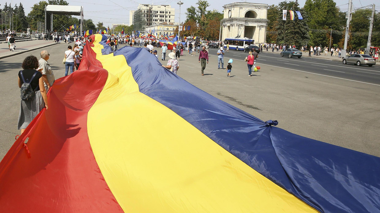 """Moldavos y rumanos extienden la bandera de Rumanía durante la """"Gran Asamblea del Centenario"""" en Chisináu, Moldavia. 1 de septiembre de 2018."""