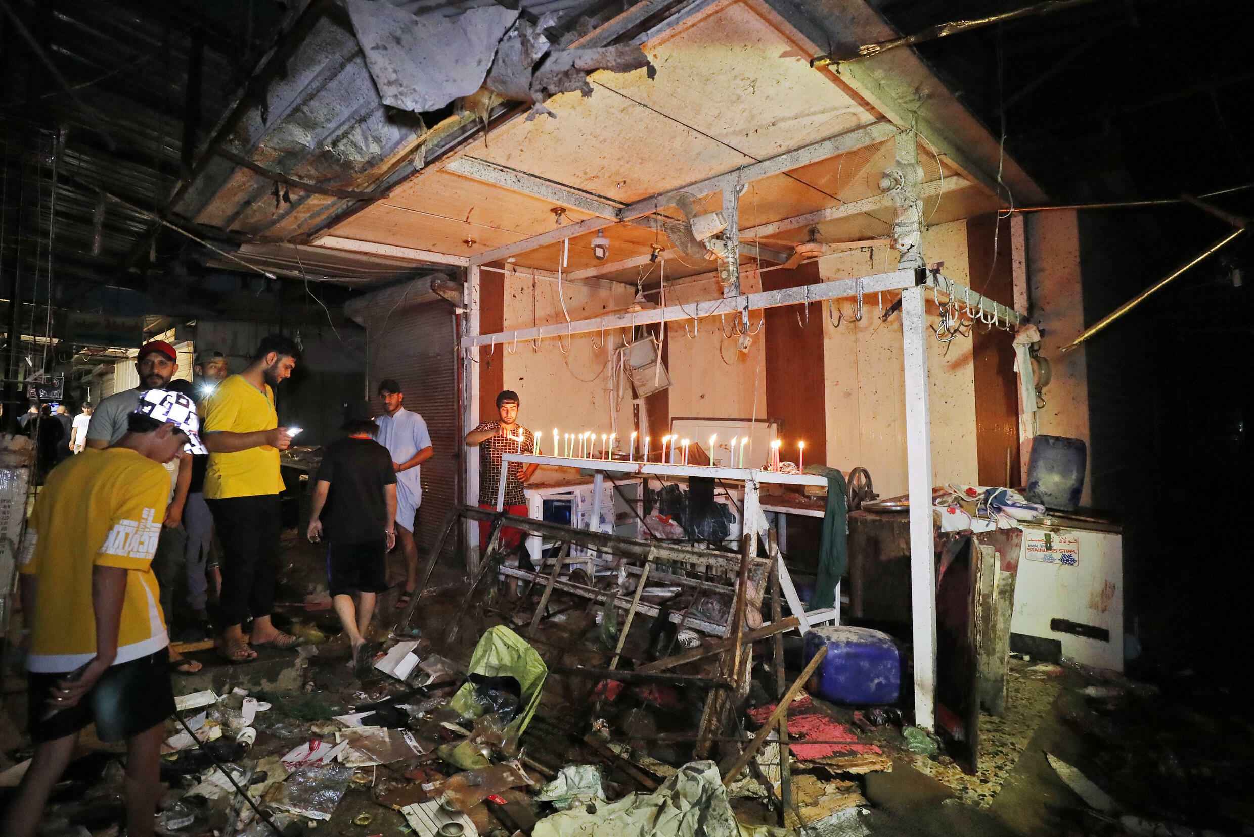 Iraqis light candles at the site of the explosion in a popular market in the mostly Shiite neighbourhood of Sadr City, east of Baghdad, on July 19, 2021